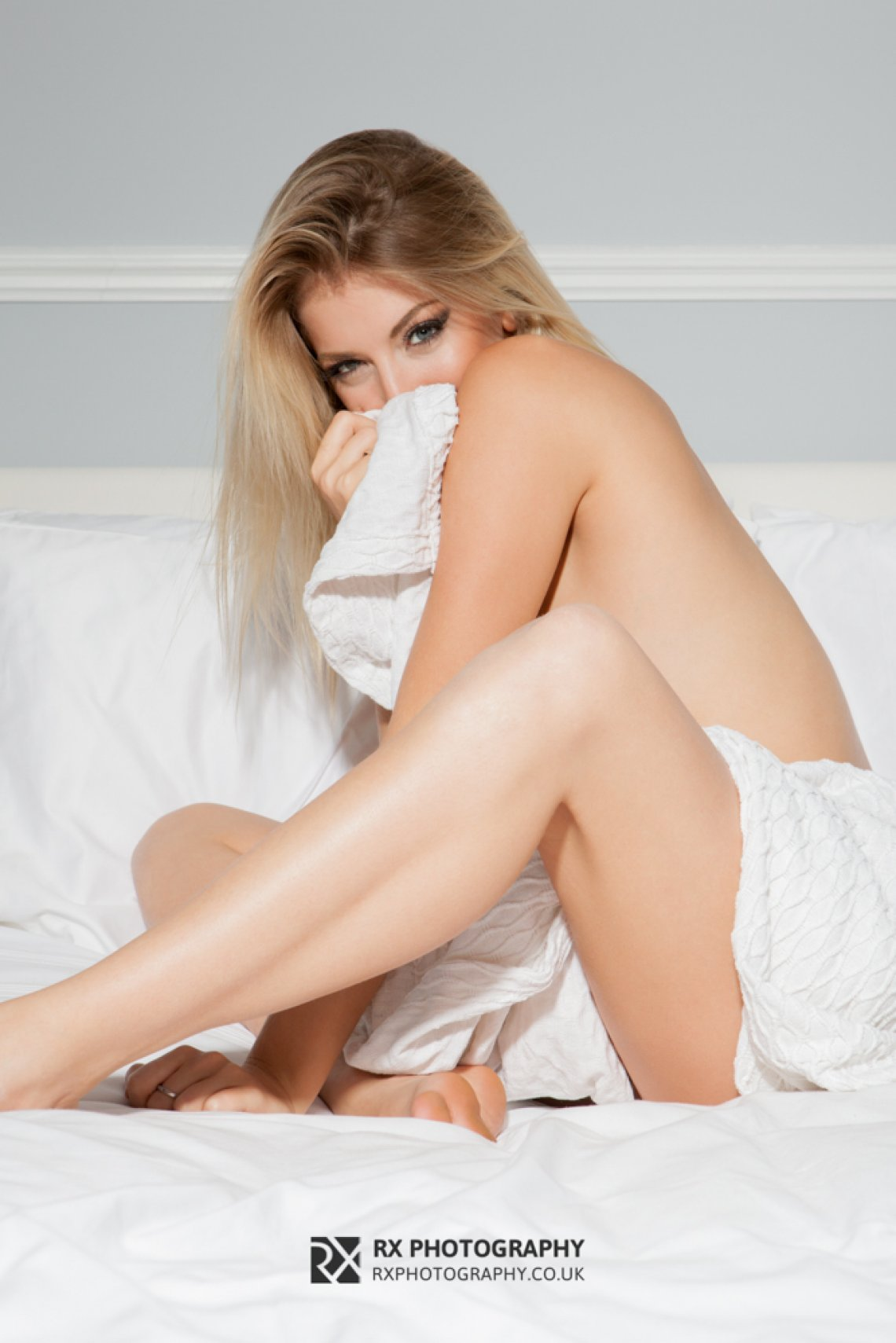 RX Photography blonde implied sexy bedsheets legs tan cheeky smile